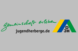 Cirka 8 Kinder stehen um ein Lagerfeuer auf einer Wiese. Sie haben Stäbe mit Stockbrot in der Hand die sie über das Lagerfeuer halten.