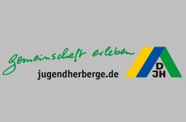 Drei Mädchen laufen über eine Wiese. Im Hintergrund sieht man einen See.